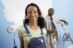Pares felizes que pintam sua casa nova Fotografia de Stock Royalty Free