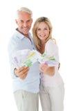 Pares felizes que piscam seu dinheiro Fotografia de Stock Royalty Free