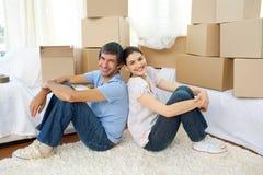 Pares felizes que relaxam ao mover a casa Fotografia de Stock Royalty Free