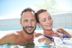 Pares felizes que relaxam na banheira de hidromassagem dos termas Fotografia de Stock Royalty Free