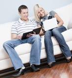 Pares felizes que relaxam no sofá imagens de stock