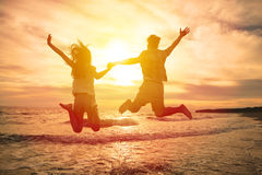 Pares felizes que saltam na praia Fotos de Stock Royalty Free