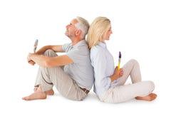 Pares felizes que sentam e que guardam pincéis Fotografia de Stock Royalty Free