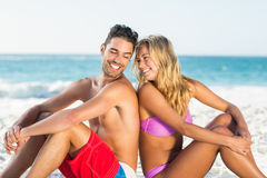 Pares felizes que sentam-se de volta à parte traseira na praia Imagens de Stock