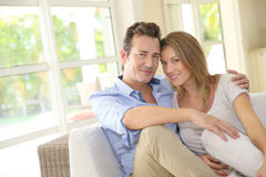Pares felizes que sentam-se em casa Imagens de Stock Royalty Free