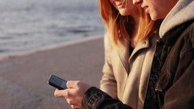 Pares felizes que sentam-se em um cais de nivelamento e que usam o smartphone video estoque
