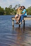 Pares felizes que sentam-se em um cais por Lago Fotografia de Stock