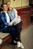 Pares felizes que sentam-se fora em um café, menina nos braços do indivíduo Sorriso fotos de stock royalty free