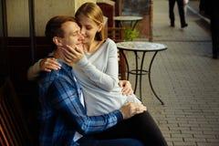 Pares felizes que sentam-se fora em um café, menina nos braços do indivíduo Sorriso fotografia de stock