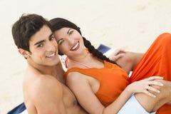 Pares felizes que sentam-se na praia Imagem de Stock