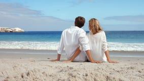Pares felizes que sentam-se na praia filme