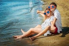 Pares felizes que sentam-se na praia Imagens de Stock Royalty Free