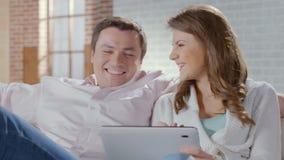 Pares felizes que sentam-se no sofá com PC da tabuleta Compra em linha video estoque