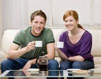 Pares felizes que sentam-se no sofá que bebe o café fresco Fotografia de Stock Royalty Free