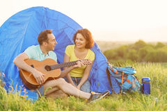 Pares felizes que sentam-se perto da barraca com guitarra Fotografia de Stock