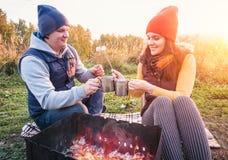 Pares felizes que sorriem e marshmallows do assado na fogueira na natureza O homem e a mulher alegres descansam no fogo Imagem de Stock Royalty Free
