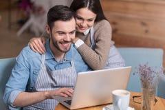 Pares felizes que sorriem e que usam o portátil Foto de Stock Royalty Free