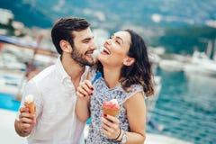 Pares felizes que têm a data e que comem o gelado em férias foto de stock