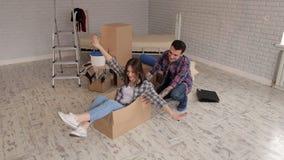 Pares felizes que têm o divertimento em um apartamento novo, menina feliz que senta-se na caixa de cartão