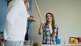 Pares felizes que têm o divertimento na cozinha que luta com concha e rolamento-pino ao cozinhar o café da manhã em casa filme