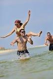 Pares felizes que têm o divertimento na praia Imagem de Stock