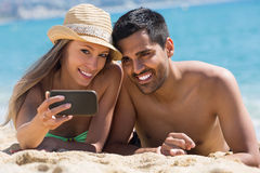 Pares felizes que tomam a foto na praia fotos de stock royalty free