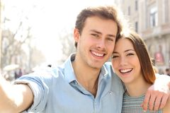 Pares felizes que tomam selfies na rua em férias de verão imagens de stock royalty free