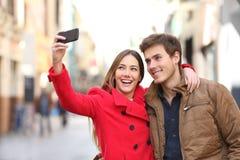 Pares felizes que tomam selfies na rua no inverno imagem de stock royalty free