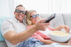 Pares felizes que vestem os vidros 3d que comem a pipoca Imagem de Stock Royalty Free