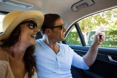 Pares felizes que viajam no carro Foto de Stock Royalty Free