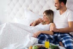 Pares felizes românticos que comem o café da manhã na cama foto de stock