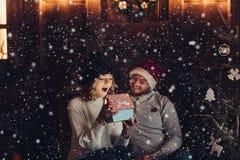 Pares felizes sob a queda de neve que olha o presente mágico foto de stock