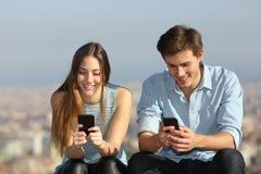 Pares felizes usando seus telefones espertos fora foto de stock