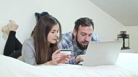 Pares felizes usando um portátil que encontra-se em uma cama em casa fotografia de stock
