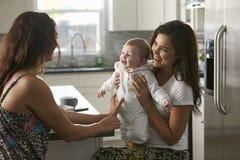 Pares femeninos que se sientan en la cocina que detiene a su bebé Fotos de archivo libres de regalías