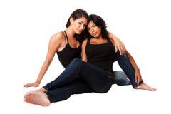 Pares femeninos que se sientan junto Imagen de archivo
