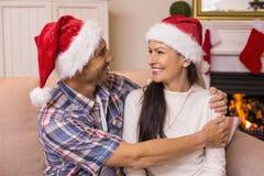 Pares festivos no chapéu de Santa que abraça no sofá Imagens de Stock