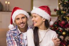 Pares festivos no chapéu de Santa que abraça no sofá Imagem de Stock
