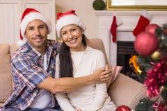 Pares festivos que abraçam no sofá Fotografia de Stock Royalty Free
