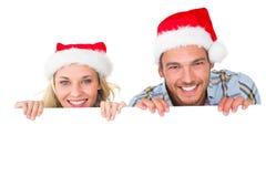 Pares festivos que sonríen de detrás el cartel Imagenes de archivo