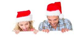 Pares festivos que sonríen de detrás el cartel Foto de archivo libre de regalías