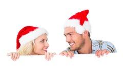 Pares festivos que sonríen de detrás el cartel Fotos de archivo libres de regalías