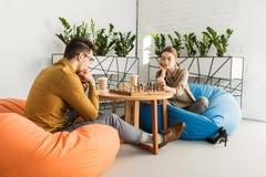 pares focalizados novos que jogam a xadrez ao sentar-se foto de stock royalty free