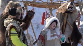 Pares fotografiados en indígenas de la ropa de Kamchatka cerca de oso relleno