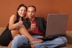 Pares frescos jovenes con la computadora portátil Fotografía de archivo