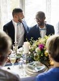 Pares gay alegres en la recepción nupcial imagen de archivo