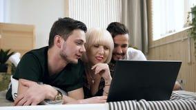 Pares gay atractivos con la novia hermosa que usa el ordenador portátil mientras que miente en el sofá con la emoción feliz en la almacen de metraje de vídeo
