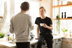 Pares gay internacionales en ropa casual por la mañana en casa en la cocina fotos de archivo