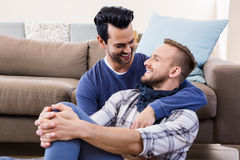 Pares gay que abrazan en el sofá imágenes de archivo libres de regalías