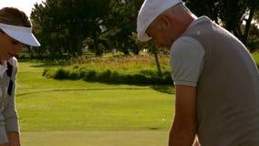 Pares Golfing en el décimo octavo agujero en el campo de golf almacen de metraje de vídeo